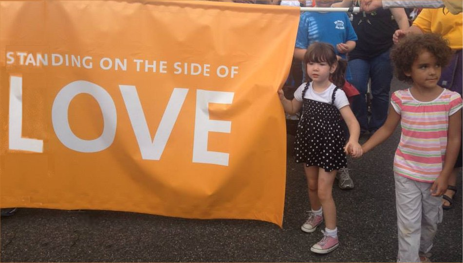 "Two girls holding hands near a ""Standing on the side of love"" banner"